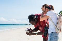 Svart man och kvinna som ser telefoner, zanzibar Royaltyfri Foto