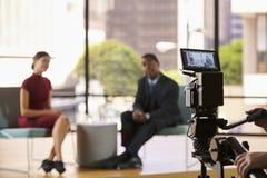 Svart man och vit kvinna på TVuppsättningen, fokus på förgrund royaltyfri bild