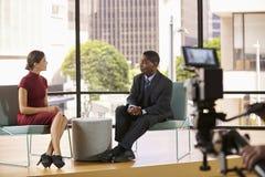 Svart man och vit kvinna på uppsättning som filmar en TVintervju royaltyfri foto