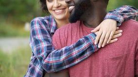Svart man och vit kvinna som tillsammans ler och ömt kramar, lyckligt folk royaltyfria bilder
