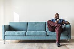 Svart man som använder mobiltelefonen på soffan royaltyfri fotografi