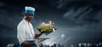 Svart man som b?r ett f?rkl?de och lagar mat i handling Blandat massmedia royaltyfri foto