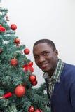 Svart man som dekorerar julgranen Fotografering för Bildbyråer