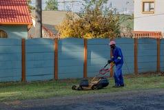 Svart man som mejar en gräsmatta på en privat uppehåll royaltyfri fotografi