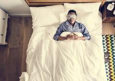 Svart man som sover på säng med ögonmaskeringen arkivbild