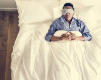 Svart man som sover på säng med ögonmaskeringen arkivfoto