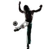 Svart manfotbollspelare som jonglerar fotbollsilhouet Arkivbild
