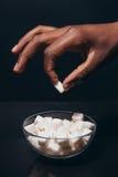 Svart manhand med det vita stycket av socker contrast arkivbild