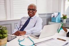 Svart manlig doktor för pensionär i ett kontor som ser till kameran royaltyfri foto