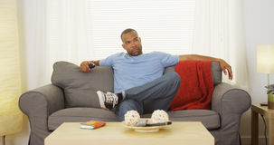 Svart mansammanträde på hållande ögonen på tv för soffa Arkivfoto