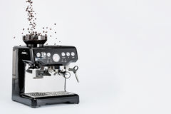 Svart manuell kaffebryggare med molar och fallande kaffebönor på vit bakgrund, sidosikt arkivfoto
