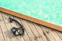Svart maskering för att snorkla på en träfläck mot azurvatten royaltyfri foto