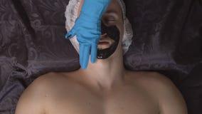 Svart maskering för framsida Bästa sikt av en avkopplad ung man som använder en svart maskering i brunnsorten lager videofilmer