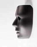 Svart maskering som dyker upp från vit bakgrund Royaltyfri Foto