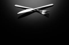 Svart matbakgrund, bestick på reflekterande yttersida med kopieringsutrymme arkivfoto