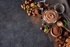 Svart matbakgrund med kakao, muttrar och choklad royaltyfria bilder