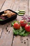 Svart matbehållare med grillade fega vingar och rå grönsaker på lantlig bakgrund royaltyfri foto