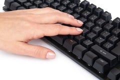 Svart mekaniskt datortangentbord med handen bakgrund isolerad white arkivfoto