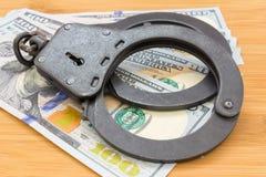 Svart metall handfängslar att ligga på de 100 dollarna sedlar Fotografering för Bildbyråer