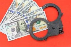 Svart metall handfängslar att ligga på de 100 dollarna sedlar på en röd bakgrund Arkivbild