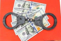 Svart metall handfängslar att ligga på de 100 dollarna sedlar på en röd bakgrund Royaltyfria Bilder