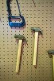 Svart metallsåg ovanför hammaren som hänger på det wood stiftet på den bruna pinnen bo Royaltyfria Foton
