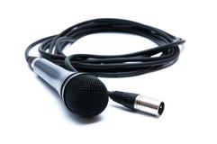 Svart mikrofon med en kabel på en vit bakgrund Arkivfoton
