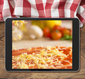 Svart minnestavlaPC med pizza som visas på trätabell- och picknickbordduk royaltyfria bilder