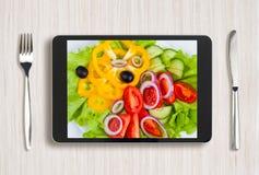 Svart minnestavlaPC med sund mat på skärmen och trätabellen arkivfoto