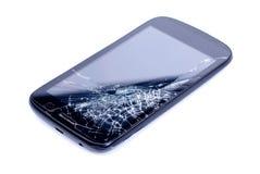 Svart mobiltelefon med en bruten skärm på en isolerad backgroun arkivbild