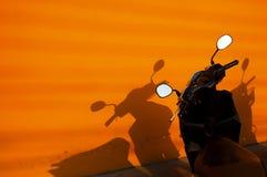 Svart motorbike nära en orange vägg royaltyfria foton