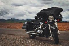 Svart motorcykel som parkeras på landsvägen Royaltyfri Fotografi