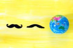 Svart mustasch och värld på tomt kopieringsutrymme för gul bakgrund för inskrift Royaltyfria Bilder