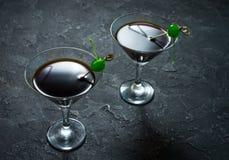 Svart nattdansare för coctail med balsam och cola som dekoreras av segment av en citron och en gräsplankörsbär arkivbilder