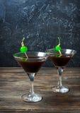 Svart nattdansare för coctail med balsam och cola som dekoreras av segment av en citron och en gräsplankörsbär arkivfoto