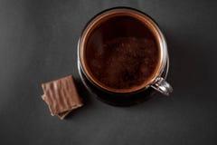 Svart naturligt doftande kaffe i den genomskinliga koppen på en svart bakgrund arkivbild