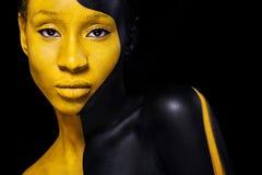 Svart och gul makeup Gladlynt ung afrikansk kvinna med konstmodemakeup fotografering för bildbyråer