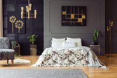 Svart och guld- affisch på ovannämnd säng för grå vägg i sovruminre med växter och fåtöljen Verkligt foto royaltyfri fotografi