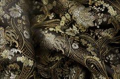 Svart och guld- fabrick för silke Arkivfoton
