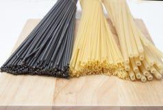 Svart och guld- spagetti, degar på ett träbräde royaltyfria bilder