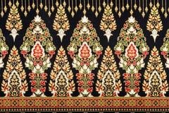 Svart och guld- thailändskt siden- tyg, bakgrund och modell Arkivbilder