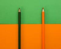 Svart och orange blyertspenna på en gräsplan- och apelsinbakgrund Arkivfoton