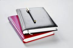 Svart och röd anteckningsbok och penna royaltyfri bild