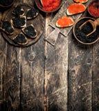 Svart och röd kaviar i gamla träbunkar arkivbilder