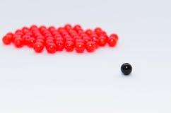 Svart och röd pärla på vit bakgrund Arkivbild