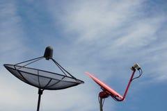 Svart och röd satellit- maträtt med den blåa himlen Arkivbilder