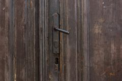 Svart och rostigt dörrhandtag för tappningmetall Gamla träbruna dörrar fotografering för bildbyråer