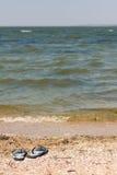 Svart och Whiet sandaler på stranden Royaltyfria Bilder