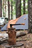Svart orange yxa i trästubben på bakgrunden av tält a arkivfoto