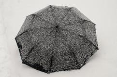 Svart paraply under tungt snöfall arkivbild